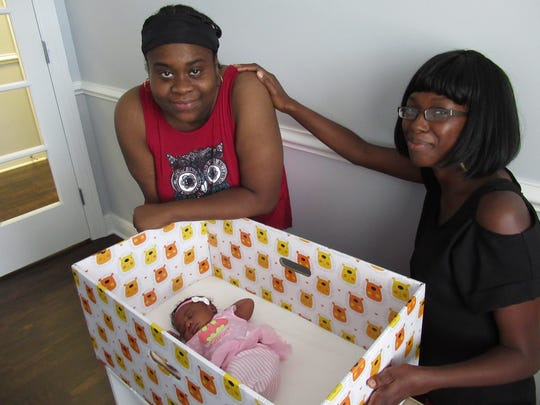 New mother Linda Wynn, left with her newborn daughter, Elizabeth Denise Gordon, in her baby box and 'Doula' Keda Henderson in 2018.