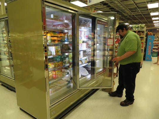 Frozen foods and dairy manager Kirk King stocks the shelves in the Lansing Market.