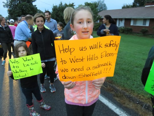Emily Ernst holds up a sign in support of a sidewalk