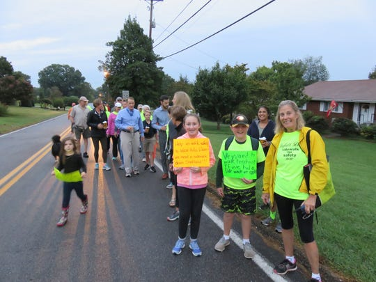Walkers in support of a sidewalk on Sheffield Drive in West Hills take a break during the jaunt to West Hills Elementary in 2017.