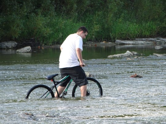 Joseph Lee, 14, of Fremont rides his bike in a newly shallow part of the Sandusky River Thursday.