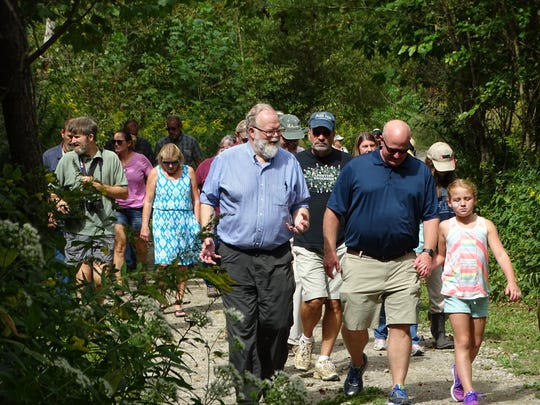 Jock Herron, center left, whose family's Herron Farms LLC is one of five property owners providing land for the new Kinnikinnick Fen Nature Preserve, walks down a trail at the preserve during the official opening of the site Saturday.