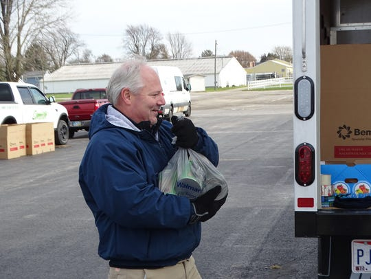 Mike Dukeshire carries food donated by locals that