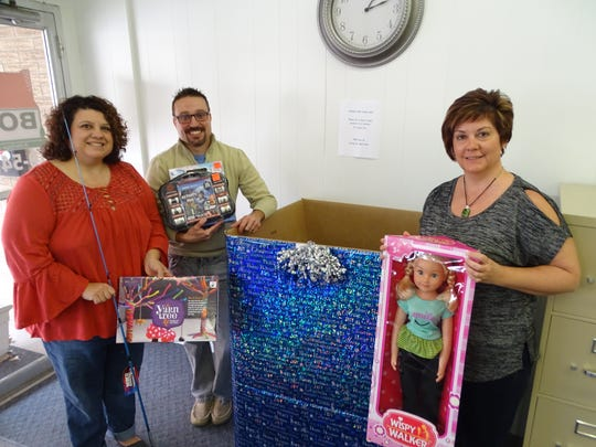 """Bolte Real Estate employees, from left, Vicki Schmitz, Mike Dziak and Monica Camarata hold up some of the Christmas toys donated at their office collection box, one of four sites for this year's """"Caring for Clyde Kids"""" Community Toy Collection."""