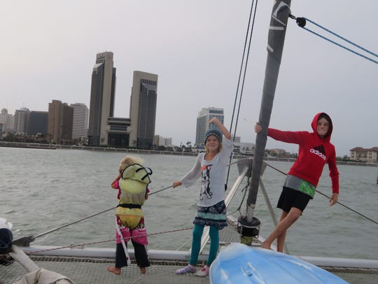 Tully Grosjean, 4, (left) Marin Grosjean, 7, and Cobin Grosjean, 11, pose for a picture as they make it to shore in Corpus Christi. The Sparkling City was their first stop on U.S. soil in over a year.