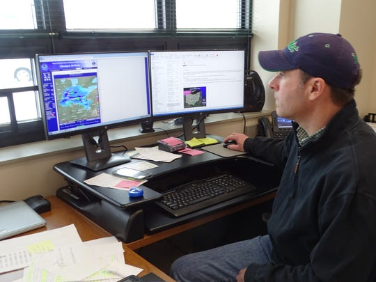 Mike Leach, transportation administrator for Ohio Department of Transportation's Fremont garage, checks local weather reports to stay on top of the snow moving into the Fremont area on Friday.