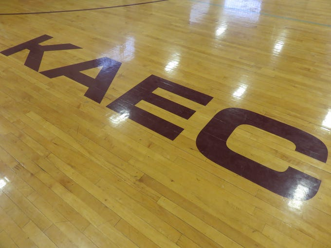 The wooden floor of the court features KAEC initials.