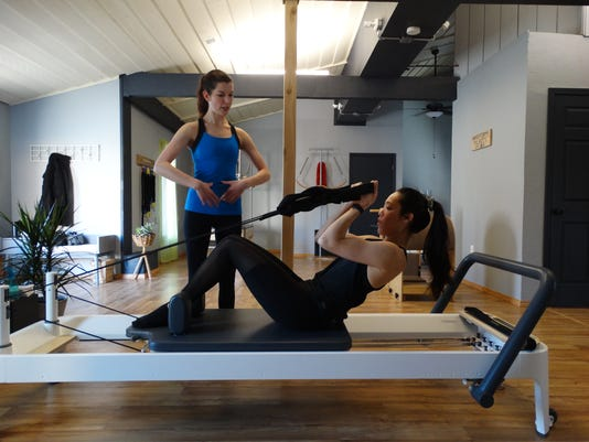 636564515783693954-Instructor-Courtney-Holcomb-teaching-Waveforms-Pilates-student-Nalani-Andres-on-the-Pilates-Reformer.JPG