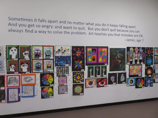 A wall of art at the All School Exhibition, accompanied by a quote from a local elementary school student.