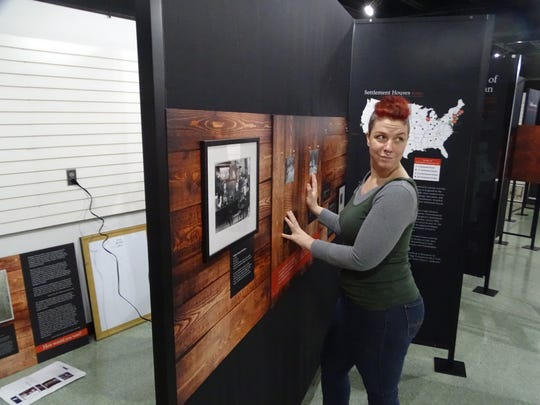 "Annie Montgomery of the Mid-America Arts Alliance holds up a panel for the new ""Jacob A. Riis: How the Other Half Lives"" exhibit that opens Friday at the Rutherford B. Hayes Presidential Library and Museums."