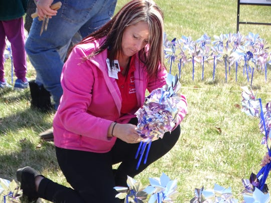 Holly Dagg of the Leadership Sandusky County Class of 2018 plants pinwheels on the lawn in front of the Sandusky County Children's Services building in recognition of April being Child Abuse Prevention Month.