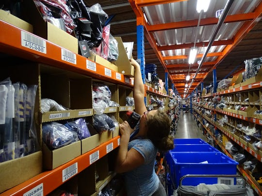 A seasonal employee works to fill orders at Fanatics