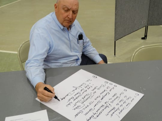 "Fremont businessman Tom Kern writes down input from residents at the city's workforce development table  at the city's ""charette sessions"" held at Terra State Community College."