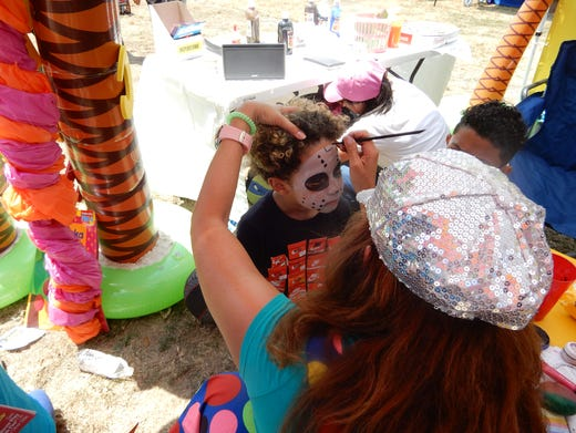 A child has his face painted at the Early Learning