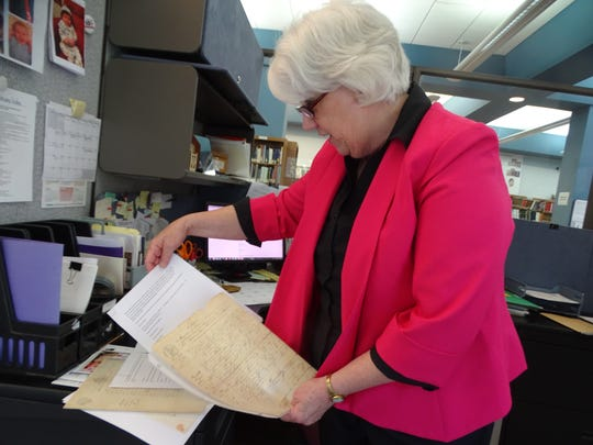 Head librarian Becky Hill shows off some donated genealogy documents at her office in the Rutherford B. Hayes Presidential Library.