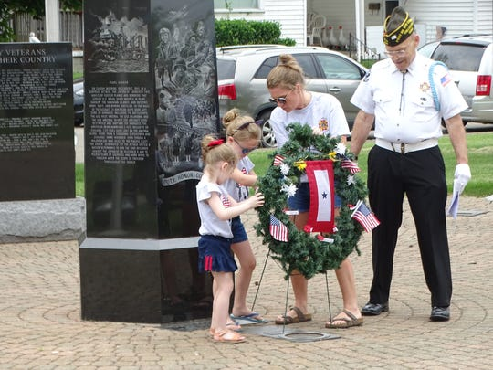 Tara Robertson and daughters, Effy and Miller, join VFW Post 108's Robert Leach in a wreath laying ceremony Saturday at Veterans Memorial Park in Chillicothe. Robertson was asked to take part in the ceremony on behalf of her husband, Brian, who served in Afghanistan and Iraq.