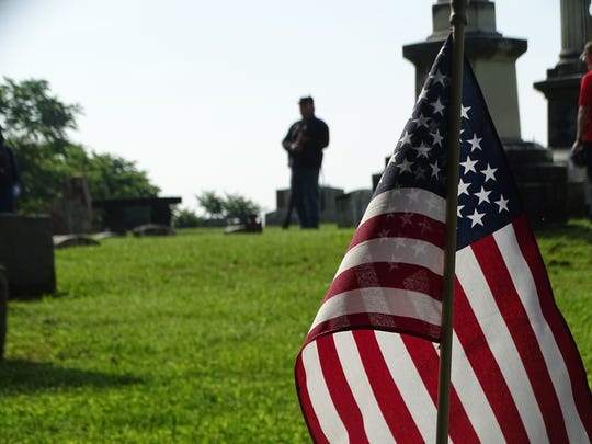 American flags adorned gravesides across Grandview Cemetery Monday morning, including this area where the procession of visitors stopped to hear about General Joshua Sill and Major Tayloe Mason from a member of the Civil War Round Table.