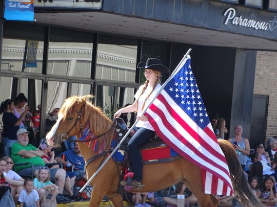 A representative from Fremont Baptist Temple's Cowboy Camp carries an American flag as she rides on horseback in the 2018 Memorial Day parade in downtown Fremont.