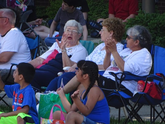 Parade spectators sit in front of Fremont's city hall