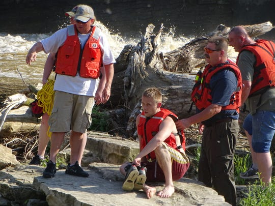 Rescuers from the Ballville Volunteer Fire Department's Water Rescue team wait to help an unidentified swimmer to the shoreline Monday. The swimmer and three of his friends had fallen into the Sandusky River near the Ballville Dam.