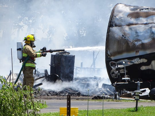 A firefighter douses a charred travel trailer with