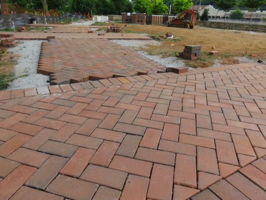 Some brick has already been laid down to make a pathway.