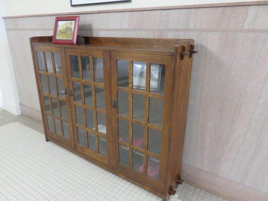 A bookcase in Tyson Place lobby stores school memorabilia.