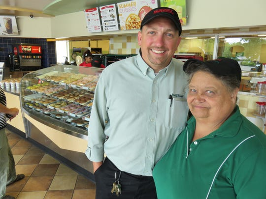 Krispy Kreme store manager Darrell Green and longtime employee Rhonda Canada stand inside the Krispy Kreme Doughnuts store on Bearden Hill.