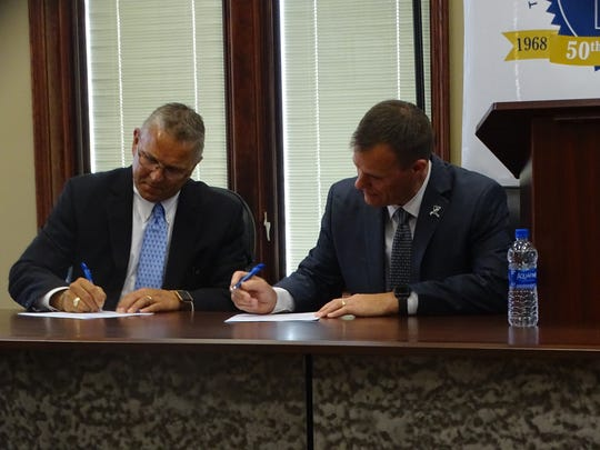 "Terra State Interim President Ron Schumacher, left, and Vanguard Sentinel Career Center Superintendent Greg Edinger sign an agreement to partner both school on a new ""pathway"" to education in eight programs."