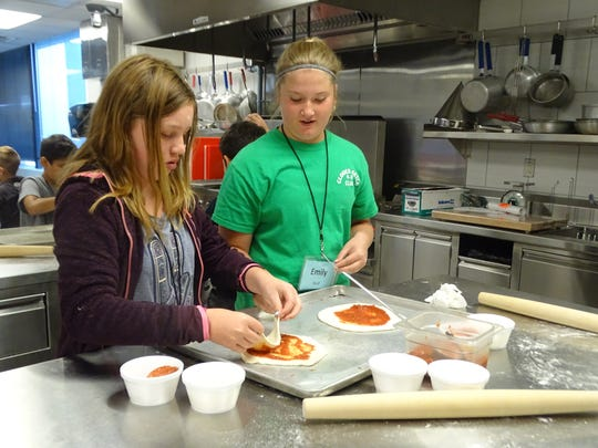 Sophia Garnica, left, and Emily Wolf discuss what kinds of toppings they want to put on the pizzas they made as part of the Pizzapalooza class.
