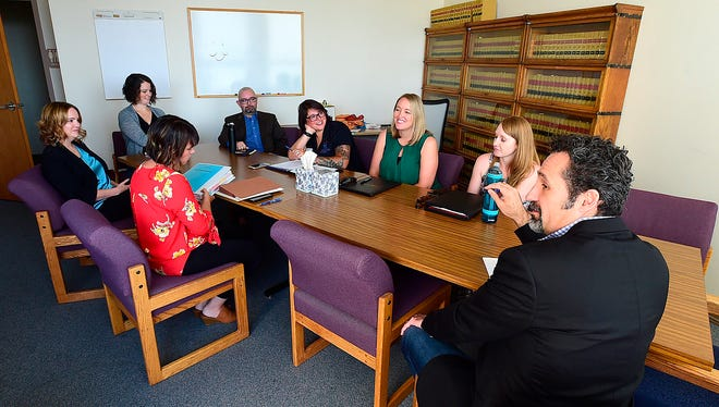 In this Friday, July 20, 2018 photo, members of Yellowstone County's Indian Child Welfare Act team, including District Court Judge Rod Souza, right, meet in a fifth floor jury room at the courthouse in Billings, Mont. (Larry Mayer/The Billings Gazette via AP)