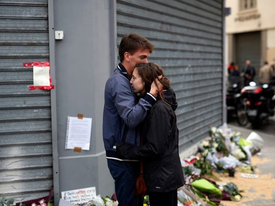 People react in front of  the Carillon cafe and the Petit Cambodge restaurant  in Paris Saturday Nov. 14, 2015, a day after over 120 people were killed  in a series of shooting and explosions.  (AP Photo/Jerome Delay)