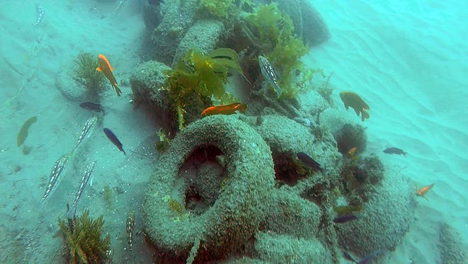 This photo provided by the California Coastal Commission and UC Davis shows a pile of scrap tires and other debris in the water off Balboa Peninsula in Newport Beach. Divers are removing hundreds of old tires, plastic jugs and other junk that were dumped off the Southern California coast nearly 30 years ago in hopes of creating an artificial reef that would serve as a home to fish and mussels.