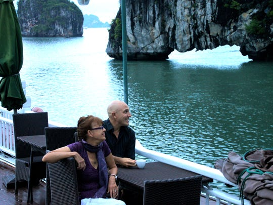 Yvonne and Thomas, owner and expedition leader of Wild Earth Expeditions, enjoy the otherworldliness of Halong Bay's misty islands from their chartered private yacht.