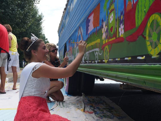 Amy Wigglesworth, this year's Mar-Del Watermelon Association Watermelon Queen, paints the side of a bus in a public art project in Laurel last month.
