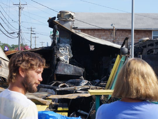 Onlookers survey the damage at Ed's Chicken and Crabs in Dewey Beach after an overnight fire on Tuesday, Aug. 9, 2016.