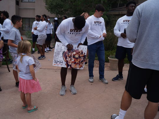 Fan gets autograph from UTEP player at picnic Saturday.