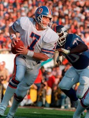 FILE - In this Jan. 25, 1987, file photo, Denver Broncos quarterback John Elway is chased by New York Giants Leonard Marshall during NFL football Super Bowl XXI in Pasadena, Calif. ( AP Photo/Amy Sancetta, File)