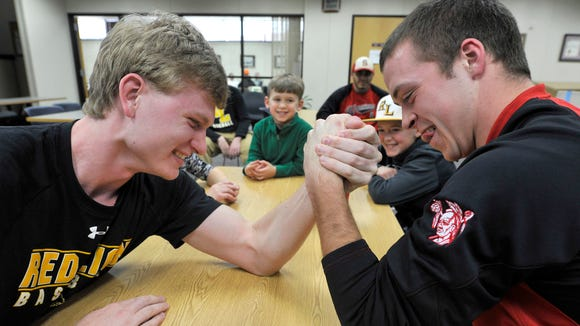 Red Lion's Wyatt Tyson, left, and Susquehannock's Connor Hood arm wrestle as the two baseball players participate in the spring sports media day sponsored by GameTimePa.com in the York Daily Record newsroom on Saturday, March 5, 2016.