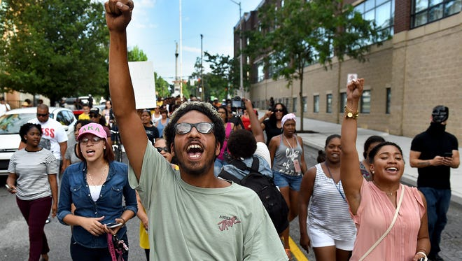 """Joelle Cora, center, and organizer Jada Richardson, right, lead a chant of """"No justice, no peace!"""" as a crowd of peaceful demonstrators make their way from Penn Park to the York City police station on Friday, July 8, 2016."""