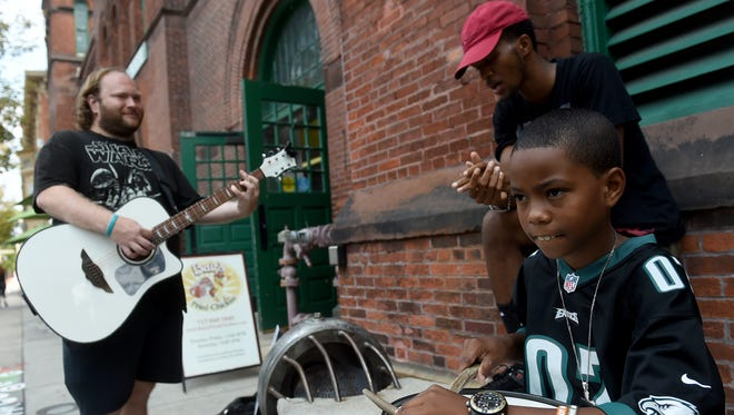 Na-Jeeb Moore, Jr., foreground, jams with his brother Trevon Woodruff, rear right, and John Beck, outside of Central Market, as the 10-year-old hopes to raise money to purchase a new drum set.