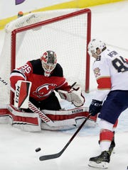 New Jersey Devils goalie Cory Schneider (35) defends his net against Florida Panthers left wing Jamie McGinn (88) during the third period of an NHL hockey game, Saturday, Nov. 11, 2017, in Newark, N.J. The Devils won 2-1.