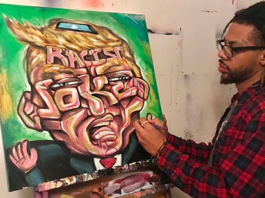 "Wilmington artist Terrance Vann paints President Trump last week with the words ""racist joke"" across his face. Vann was inspired by Trump's comments about Haiti and Africa."