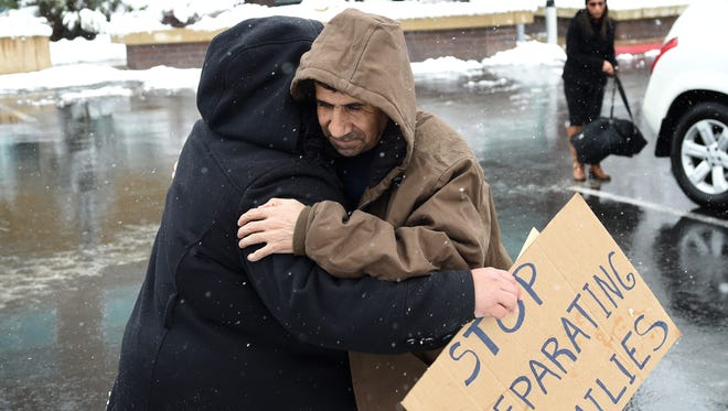 Alejandra Hernandez Chavez, left, gives David Chavez-Macia a hug as he arrives at the ICE office to turn himself in to be deported to Mexico after living in the U.S. for the past 30 years. Chavez-Macia has been on house arrest pending his deportation.