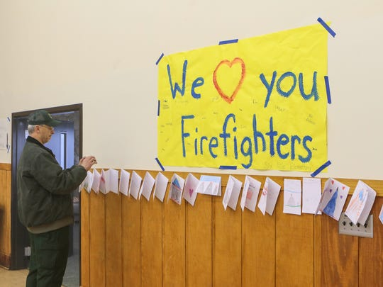 Mike Bozzo, incident commader for the South Carolina Forestry Commission looks at thank you cards from Six Mile Elementary School, posted in the assembly hall at the Wesleyan Camp at Table Rock State Park in Pickens on Friday.