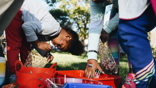 Trinidee Thompson, 5, puts a tootsie roll into her candy bag after winning two treats during a balloon popping game at a voting event hosted by People's Defense in Douglass Park on Sunday evening.