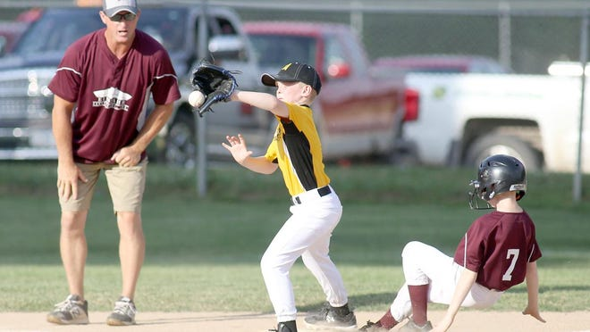 Einspahr Construction's Austin Gately beats the throw to third while Bradley Automotive third baseman Henry Brownfield takes the throw from the catcher in the second inning Monday night in Cal Ripken Minor at the Cooper County Baseball Association ballfield at Harley park.