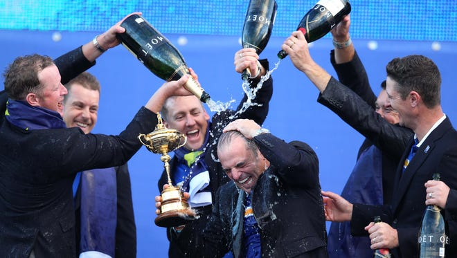 (From left) European players Jamie Donaldson, Ian Poulter, and Lee Westwood pour champagne on coach Paul McGinley  after winning the Ryder Cup on day three during the 2014 Ryder Cup at Gleneagles Resort - PGA Centenary Course.