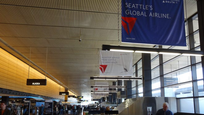 Delta Air Lines banners hang over Alaska Airlines' check-in area at Seattle-Tacoma International Airport on March 24, 2014.