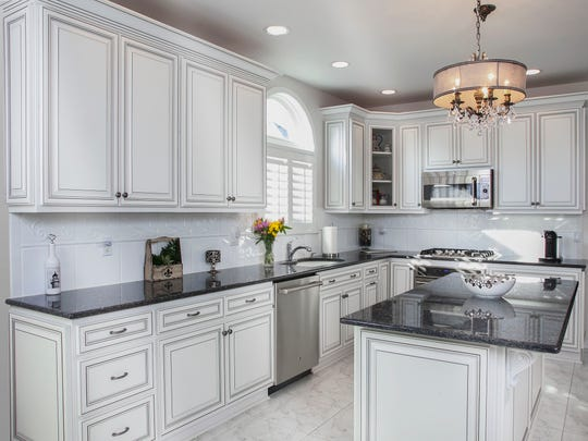 This refaced kitchen is in a traditional Vintage style in frosty white with black glazing. The countertops are existing black granite for an enriched and sophisticated new motif.